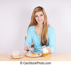 woman eating breakfast - young woman spreading marmelade on...