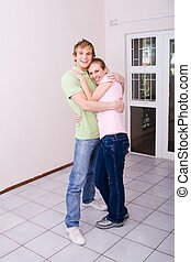 couple in unfurnished apartment - a happy couple standing in...