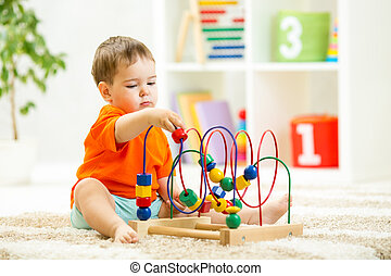 kid boy plays with educational toy indoors