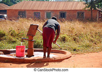 A woman and pump water from a public...