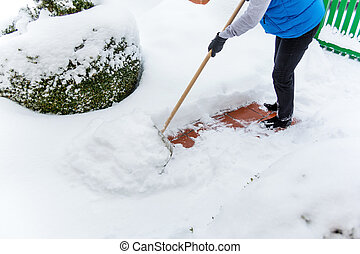 woman shoveling snow during - a woman shoveling the new snow...