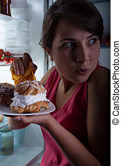 Eating in secret - Young beautiful woman eating cakes in...