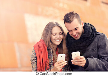 Young couple sitting on a bench and using smartphones