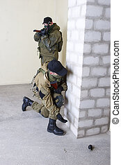 insurgents with AK 47 throws a grenade inside the building