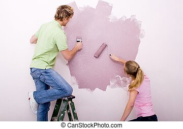 couple working hard - a couple working hard to paint the...