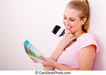 woman choosing paint colors - a woman holding a paintbrush...