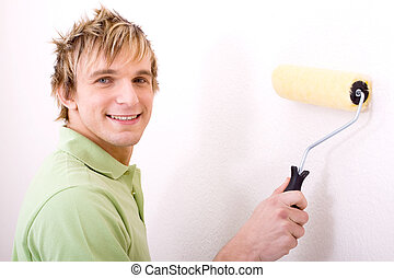 man painting wall - a blonde man painting the wall with a...