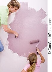 couple painting together - a blonde couple painting wall...