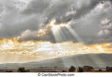 Golden sunset through clouds over dramatic sky in landscape...