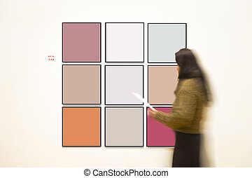 Woman in art gallery watching paintings on wall