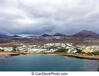aerial of Arrecife with volcanoes in clouds