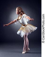 Adorable little ballerina dancing in studio