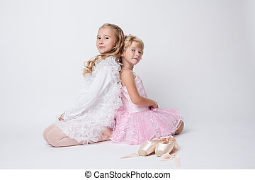 Blonde sisters posing with pointes in studio, on gray...