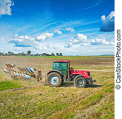 agriculture processing tractor with plow on field in autumn