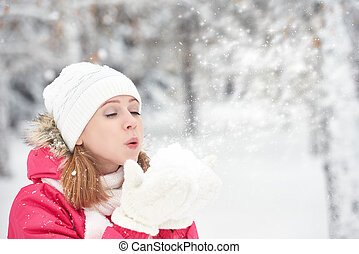 happy girl on a frosty winter walk on street blows snow from...