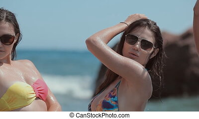Luxurious models in bikini standing at the sea in the spray...