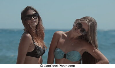 Two amazing models in swimsuits sprinkling and having fun in...