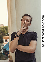 Handsome young man smoking cigarette