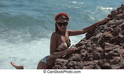 Girl with a colorful bikini and flowers on his head staing...