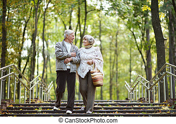Happy elderly couple on the walk in park