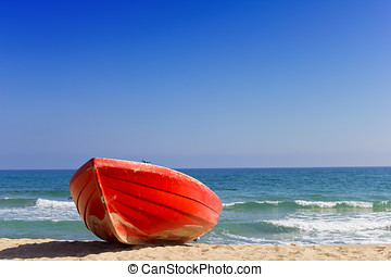 Red boat on beach near to sea