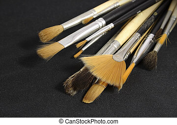 Set of art brushes located on a black piece of a fabric