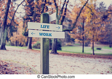 Opposite directions towards life and work - Signpost in a...