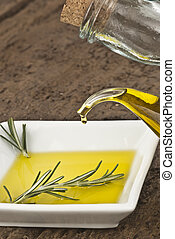 Pouring virgin olive oil in a plate with rosemary in a plate...