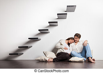 Couple at home sitting on stairs Pregnancy - Couple at home...