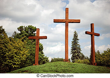 Three Crosses - Three large wooden crosses on a grassy hill.