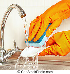 Hands in rubber gloves with sponge wash dirty dishes under...