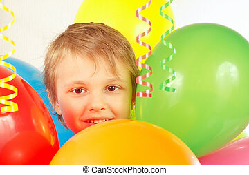 Little boy with holiday balloons and streamer