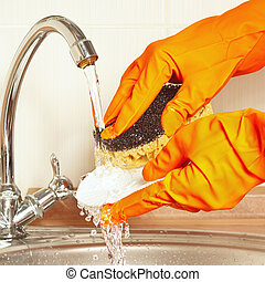 Hands in rubber gloves with sponge wash dirty plate under...