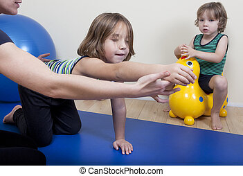 Physiotherapy with two children - a female physiotherapist...