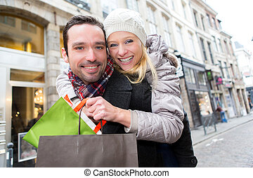 Young attractive couple having fun while shopping - View of...