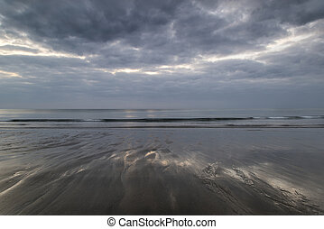 Moody ramatic sky reflected on wet beach landscape