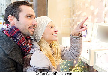 Young attractive couple doing some window shopping - View of...