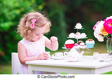 Little girl at tea party - Adorable funny toddler girl with...