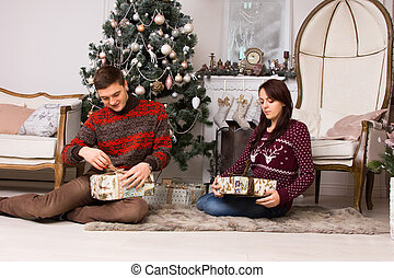 Young couple unwrapping their Christmas gifts - Young couple...