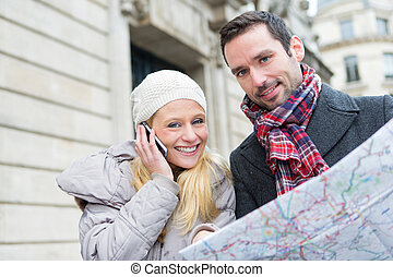 Couple of young attractive tourist watching map - View of a...