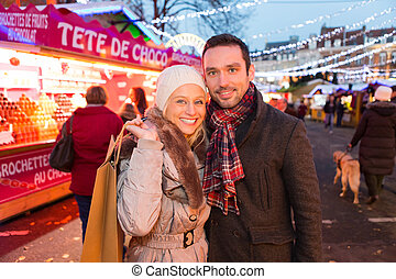 Young attractive couple in a christmas market - VIew of a...