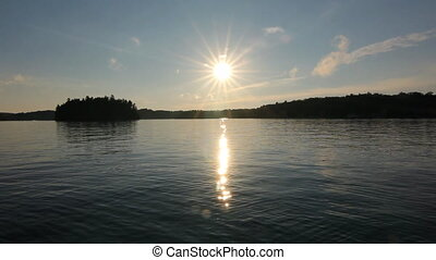 Muskoka summer lake. - Sun reflected in the lake. Sun going...