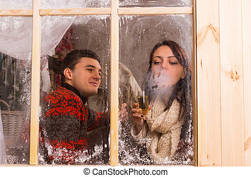 Young couple celebrating in a winter cabin - View through...