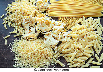 Italian pasta in variety types and shapes on wooden board