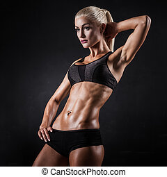 Fitness model - Beautiful athletic woman showing muscles on...
