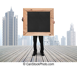 businessman holding black blank chalkboard with skyscraper...