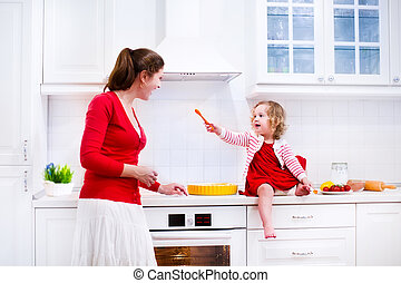 Mother and daughter baking a pie - Young mother and her...