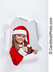 Little girl in Santa Claus outfit giving thums up sign -...