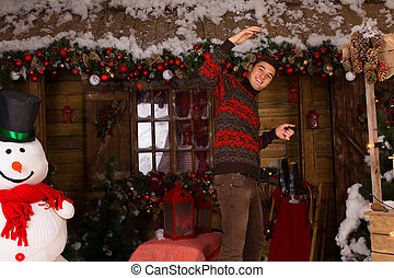 Man Holding Skates in front of Log Cabin in Winter