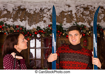Couple with Skis Standing in front of Log Cabin
